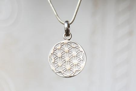 Silberner Anhänger der heiligen Geometrie der Blume des Lebens auf natürlichem weißem Hintergrund Standard-Bild