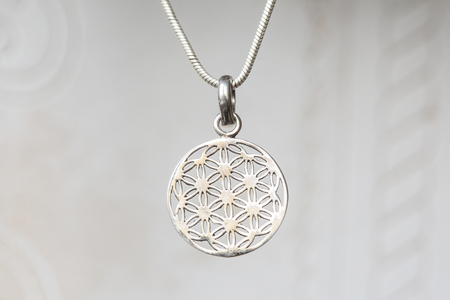 Silver flower of life sacred geometry pendant on natural white background