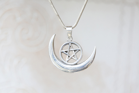 Silver pentagram in moon pendant on natural white background Imagens