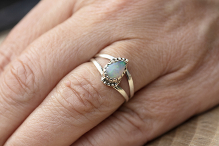 Silver ring with opal gemstone caboshon on female hand Stockfoto