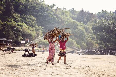 Kudli beach at Gokarna, India, January 15, 2018: Indian women walking by the beach, carrying firewood on their heads Editorial