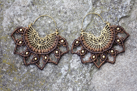Metal macrame earrings on rocky background Stock Photo