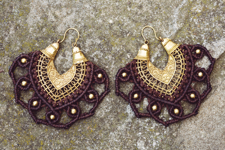Brass metal macrame earrings on rocky background