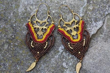 Brass metal earrings with macrame on rocky background