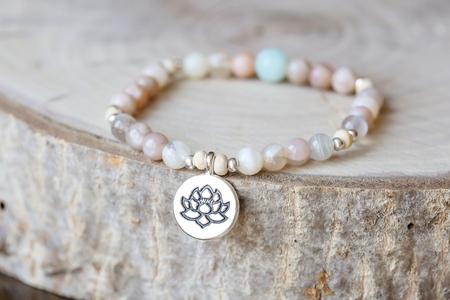 Bransoletka z kamieni mineralnych z kamieniami słonecznymi i lotosem na naturalnym drewnianym tle Zdjęcie Seryjne