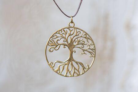 Brass metal tree shape pendant round mandala on neutral background