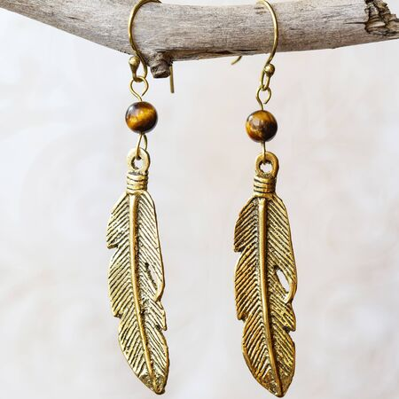 Mineral stone tyger eye and pearl beads feather shape earrings on neutral background Stock Photo
