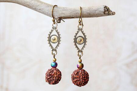 Mineral stone hematite and rudraksha beads earrings on neutral background