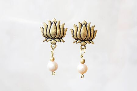 Pearl beads lotus shape earrings on neutral background Stock Photo