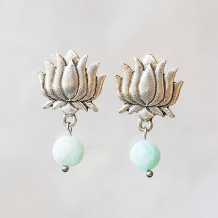 Mineral stone amazonite beads lotus shape earrings on neutral background Stock Photo
