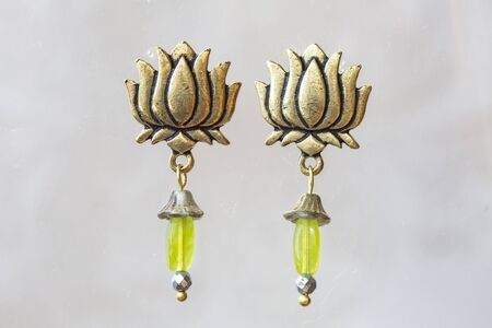 Mineral stone olivine beads lotus shape earrings on neutral background Stock Photo