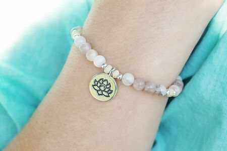 Mineral sun stone beads bracelet with lotus pendant on female wrist