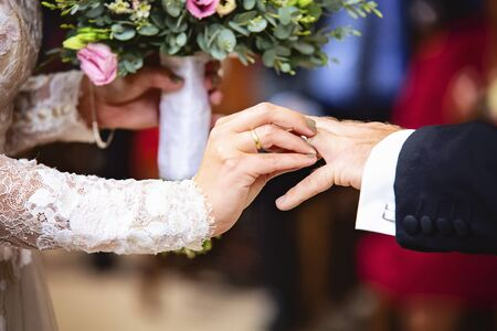 Bride hand putting a wedding ring to her groom finger Stock Photo