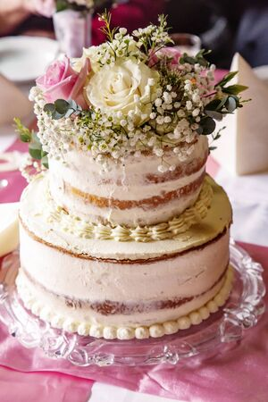Wedding cake placed on a table with real flowers Stock Photo