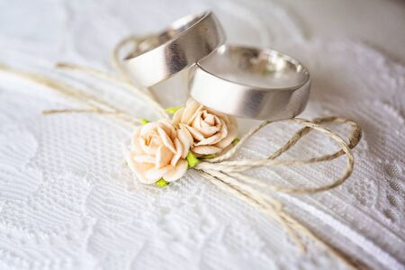 Wedding ring on lace pillow with sweet artificial small rose blossoms Stock fotó - 129082754