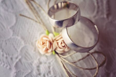 Wedding ring on lace pillow with sweet artificial small rose blossoms