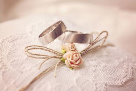 Anillo de bodas sobre almohada de encaje con dulces flores de rosas pequeñas artificiales Foto de archivo