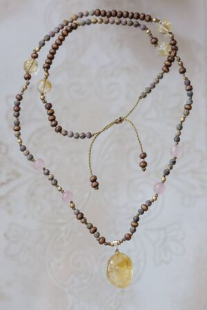 Citrine mineral stone pendant natural beads necklace on neutral background Stock Photo