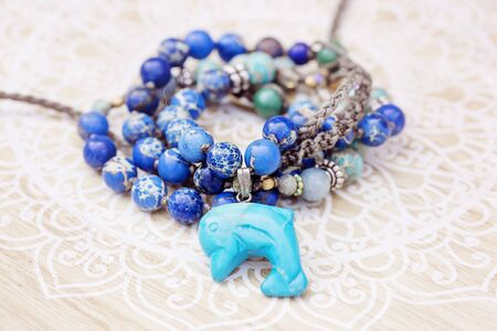 Dolphin mineral stone turquoise pendant bead necklace on decorative background Stock fotó - 129394404