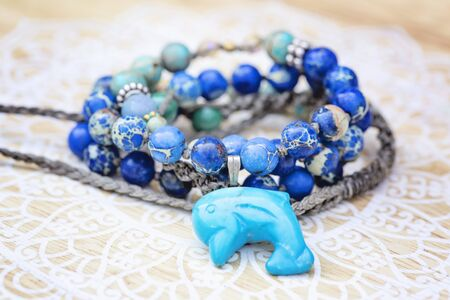 Dolphin mineral stone turquoise pendant bead necklace on decorative background Stock fotó - 129394402