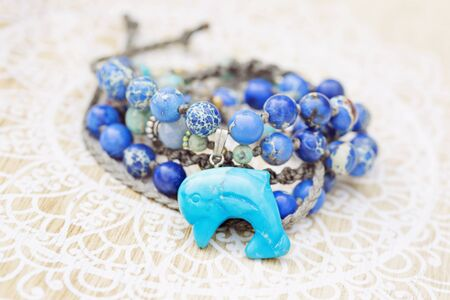 Dolphin mineral stone turquoise pendant bead necklace on decorative background
