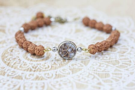 Mother pearl natural bead rudraksha seed bracelet on decorative background Stock fotó - 129394407