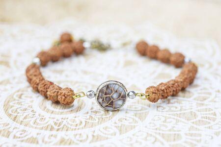 Mother pearl natural bead rudraksha seed bracelet on decorative background Stock fotó - 129394420