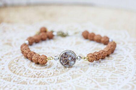 Mother pearl natural bead rudraksha seed bracelet on decorative background