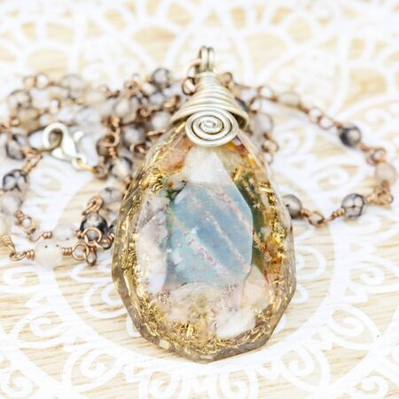 Orgonite pendant on mineral stone chain necklace placed on decorative background Stock fotó - 129394445