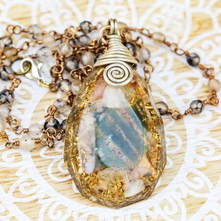Orgonite pendant on mineral stone chain necklace placed on decorative background Stock fotó - 129394447