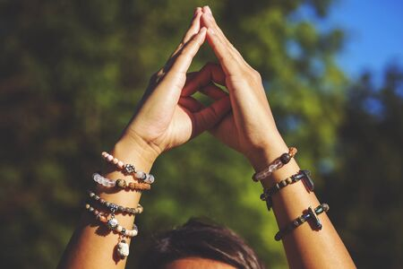 Female hands in yoga mudra and natural mineral stone bead bracelets