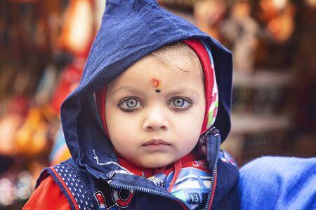 Pushkar, Rajasthan in India, Fenruary 13, 2019: Little Indian child visiting holy lake in Pushkar city