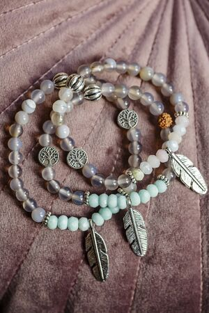 Metal feather pendant mineral faceted stone bead bracelets on pink velvet background