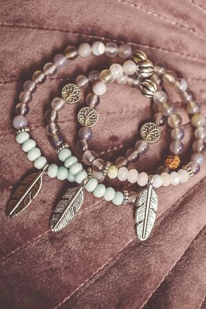 Metal feather pendant mineral faceted stone bead bracelets on pink velvet background Stock fotó - 132368999