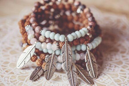 metal feather pendant mineral stone yoga bracelets on decorative natural boho background