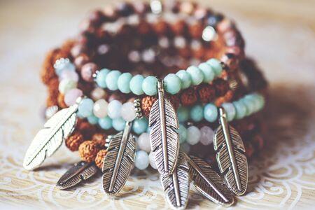 metal feather pendant mineral stone yoga bracelets on decorative natural boho background Stock fotó - 132368998