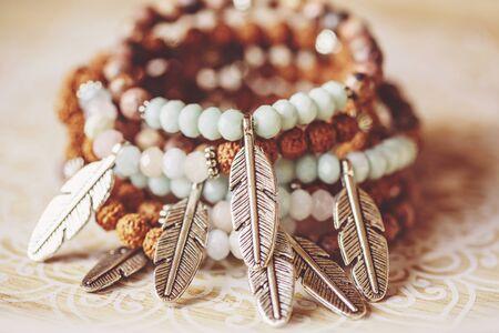 metal feather pendant mineral stone yoga bracelets on decorative natural boho background Stock fotó - 132369008