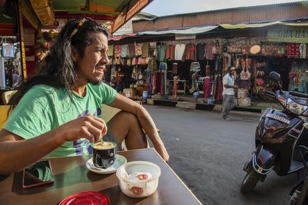 Pushkar, Rajasthan in India, January 25, 2019: Latin American tourist drinking coffee in center of Pushkar city, looking on the street Sajtókép