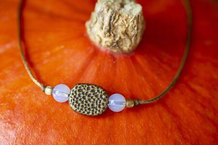 Tiny mineral stone bracelet on string placed on orange hokaido pumpkin