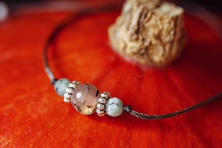 Tiny mineral stone bracelet on string placed on orange hokaido pumpkin Stock fotó - 132480844