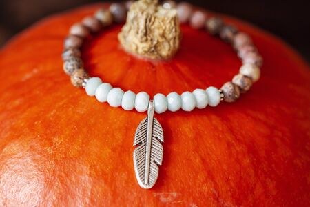 Tiny mineral stone bracelet on string placed on orange hokaido pumpkin Stock fotó - 132480926