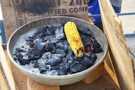 Yellow corn roasted on fire in black carbons