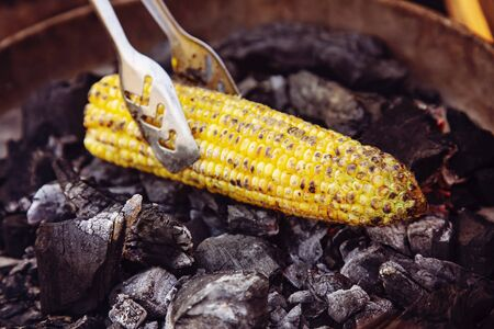 Yellow corn roasted on fire from black carbons