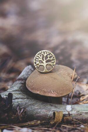 Brass tree shape ring on edible mushroom in forest