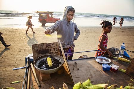 Arambol, Goa, India, February 1, 2019: Indian woman preparing roasted sweet yellow corn at the beach Sajtókép
