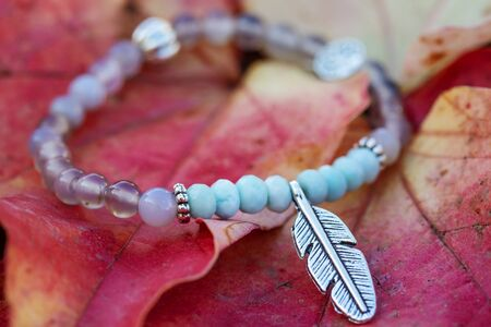 Metal feather pendant mineral stone bracelet on autumn background