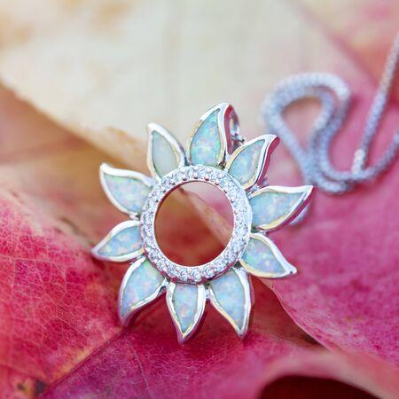 Colgante de plata con piedra mineral de ópalo blanco sobre fondo de otoño
