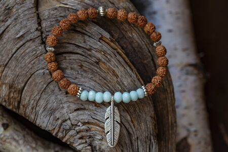 Mineral stone yoga bracelet with metal feather pendant on wooden background