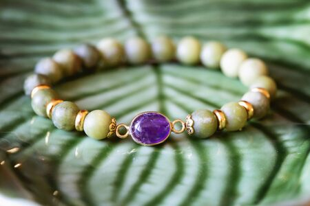 Amethyst mineral stone jade mineral beads fashionable bracelet on green background