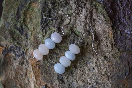 Faceted mineral stone morganite sterling silver earring on rocky background